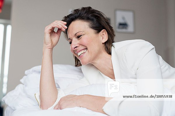 Portrait of mature woman lying on bed laughing