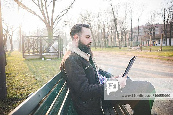 Junge bärtiger Mann mit digitalen Tablette auf Parkbank