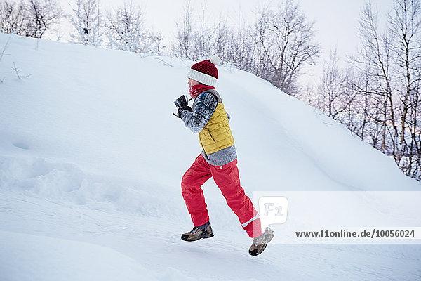 Junge rennt den schneebedeckten Hügel hinauf,  Hemavan,  Schweden