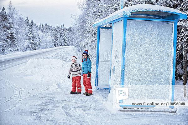 Zwei Brüder warten an der schneebedeckten Bushaltestelle,  Hemavan,  Schweden