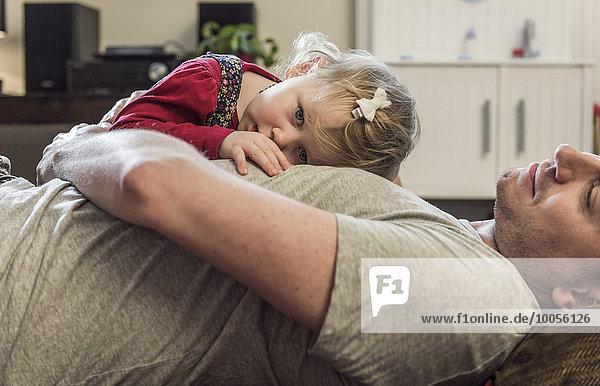 Tochter auf der Brust des Vaters liegend
