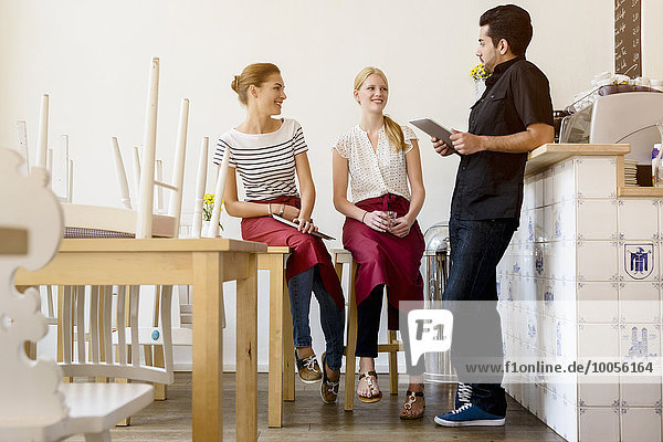 Three people planning work in cafe