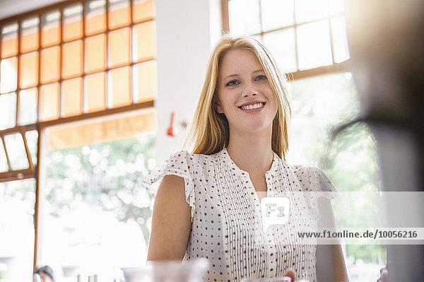 Junge blonde Frau lächelnd