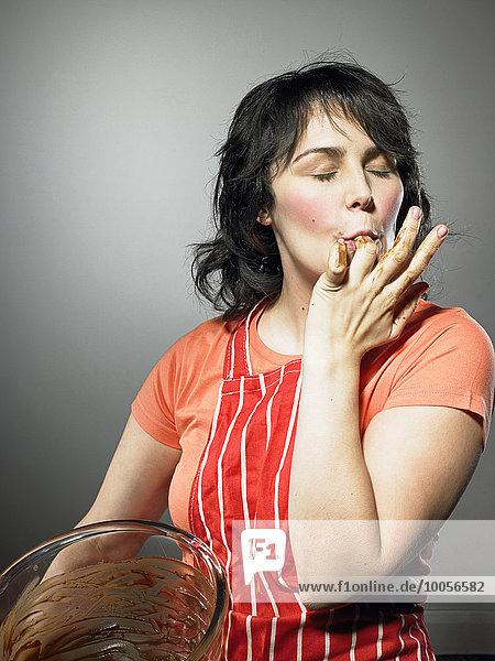 Studioaufnahme einer jungen Frau mit geschlossenen Augen  die Schokolade von den Fingern leckt.