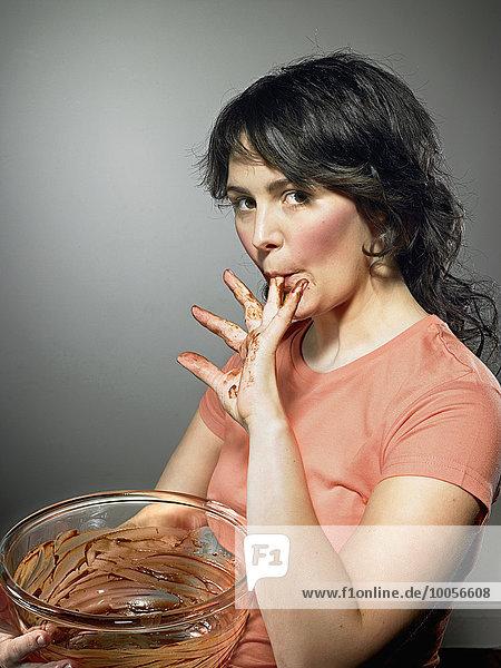 Studioaufnahme einer jungen Frau mit Rührschüssel  die Schokolade von den Fingern leckt. Studioaufnahme einer jungen Frau mit Rührschüssel, die Schokolade von den Fingern leckt.