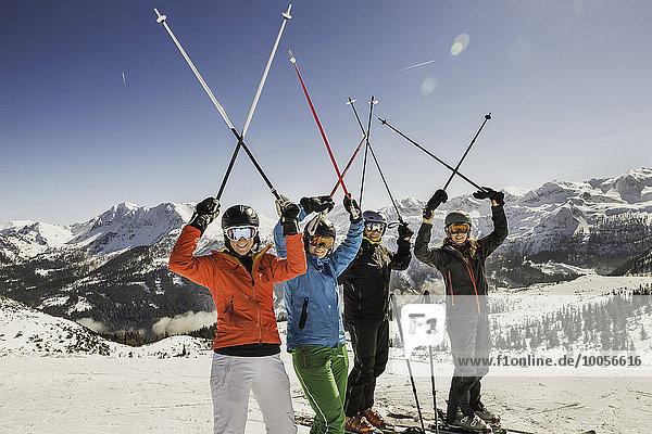 Porträt von Skifahrern auf der Piste  die Skistöcke in der Luft halten.