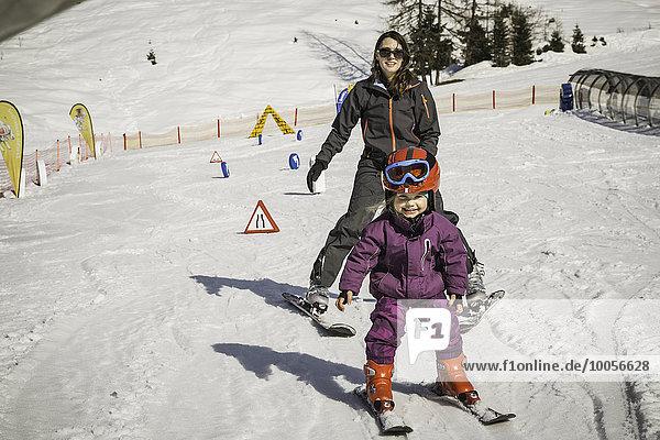 Mutter und Tochter beim gemeinsamen Skifahren  lächelnd