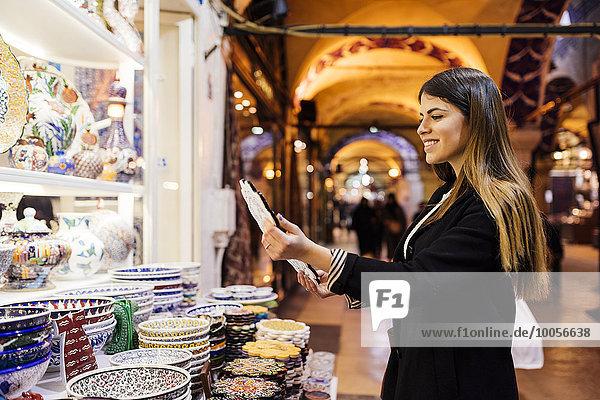 Junge Frau beim Anblick von Geschirr am Marktstand  Istanbul  Türkei