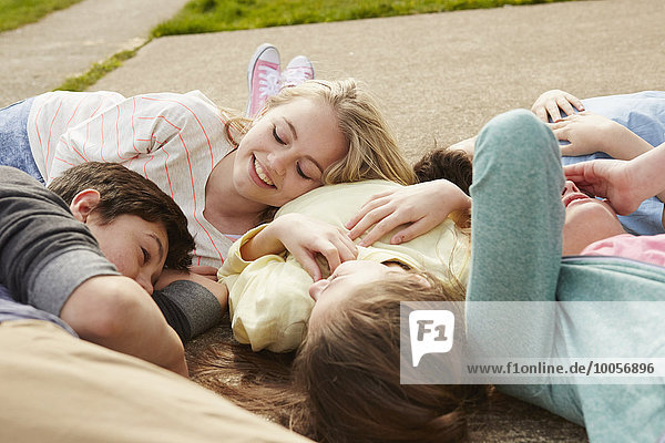 Five boys and girls lying together on path