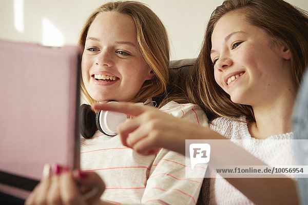 Zwei Mädchen auf dem Sofa lachend und zeigend auf digitales Tablett