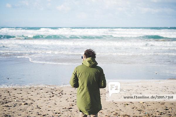 Rückansicht des Mannes mit Blick aufs Meer vom windigen Strand  Sorso  Sassari  Sardinien  Italien