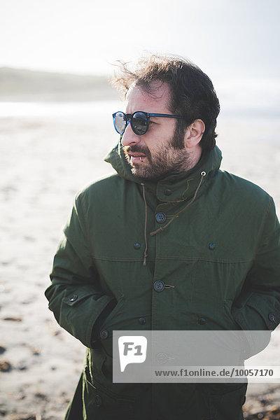 Mittlerer Erwachsener Mann mit Sonnenbrille am windigen Strand  Sorso  Sassari  Sardinien  Italien