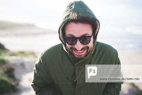 Porträt eines erwachsenen Mannes in Kapuzenjacke an der Küste