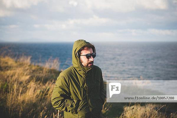 Mittlerer Erwachsener Mann  der an der windigen Küste entlang schlendert  Sorso  Sassari  Sardinien  Italien