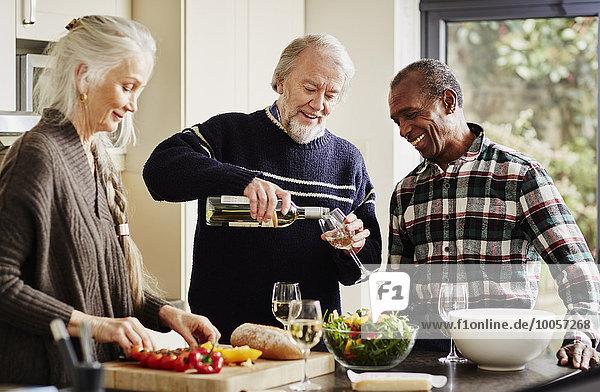 Senior man pouring wine in kitchen  woman preparing food
