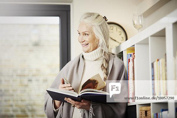 Seniorin beim Lesen zu Hause
