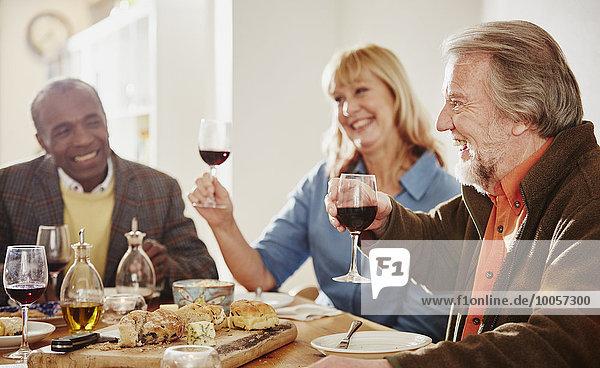 Seniorenfreunde  die beim Abendessen einen Toast aussprechen.
