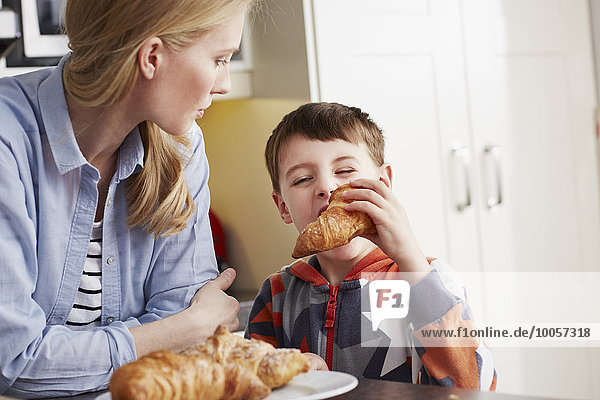 Boy biting croissant  mother watching