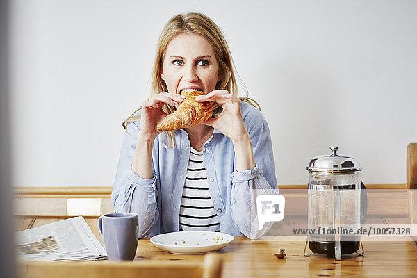 Mittlere erwachsene Frau beim Croissantessen