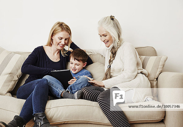 Young boy using digital tablet with mother and grandmother