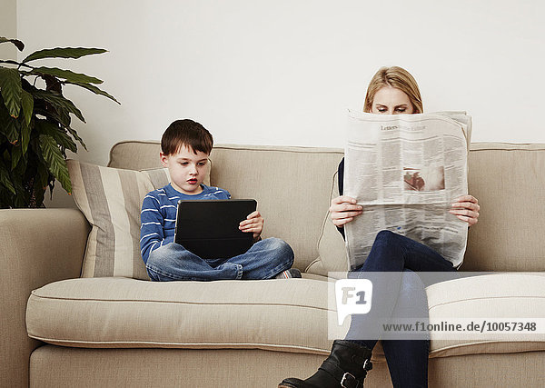 Young boy using digital tablet  mother reading newspaper