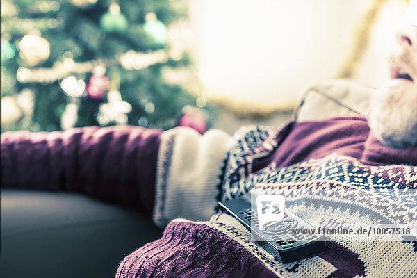 Mann mit Pullover im Schlaf mit Fernbedienung auf der Brust
