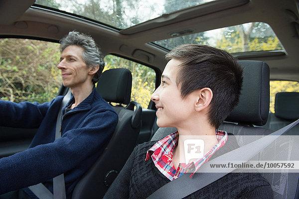 Teenager-Junge schaut Vater an  während er Auto fährt.