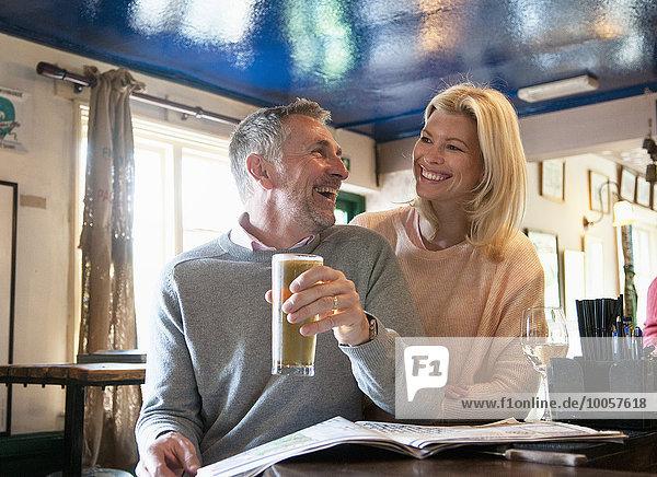 Paar lacht und liest Zeitung in der Kneipe