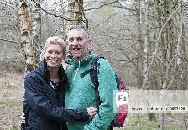 Porträt eines Wanderpaares beim Waldspaziergang