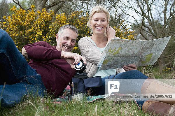 Wanderpaar liest Karte auf Picknickdecke