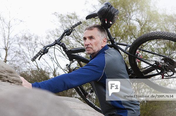 Reife männliche Mountainbiker mit Fahrrad über Felsformation