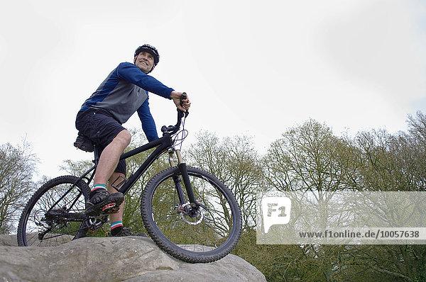 Tiefblick auf den männlichen Mountainbiker mit Blick aus der Felsformation