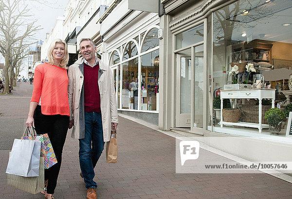 Paar mit Einkaufstaschen auf der Dorfstraße