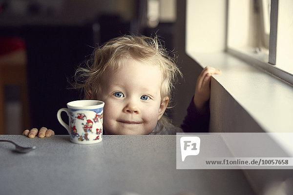 Porträt eines weiblichen Kleinkindes mit Blick von der Frühstückstheke in der Küche