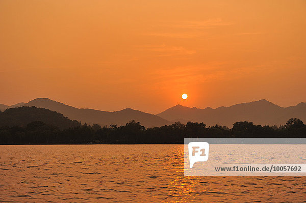 Sonnenuntergang über dem See  Berge in der Ferne  Hangzhou  China