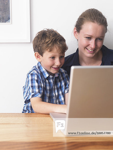 Young woman and son using laptop together at home