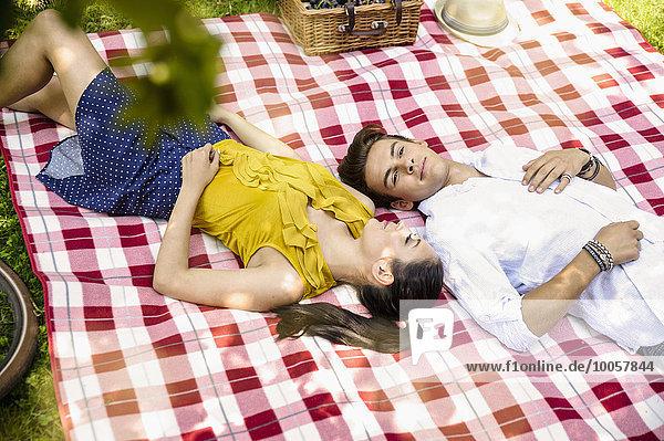 Junges Paar auf Picknickdecke liegend
