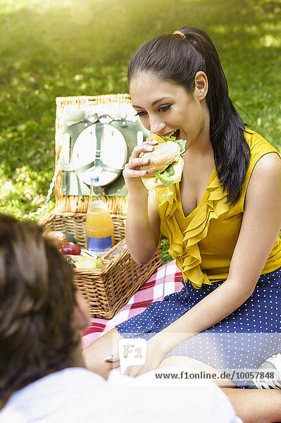 Junge Frau beim Picknick beim Sandwichessen