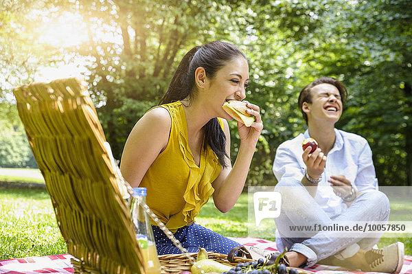 Junges Paar sitzend beim Picknick lachend
