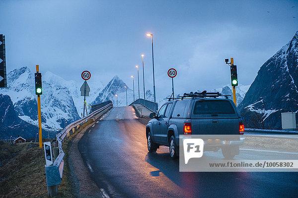 Vehicle crossing green light bridge at dusk  Reine  Lofoten  Norway