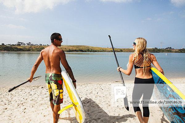 Paar tragende Paddelbretter am Strand  Carlsbad  Kalifornien  USA