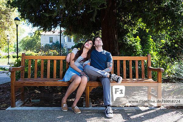 Junges Paar  das von der Parkbank aufblickt