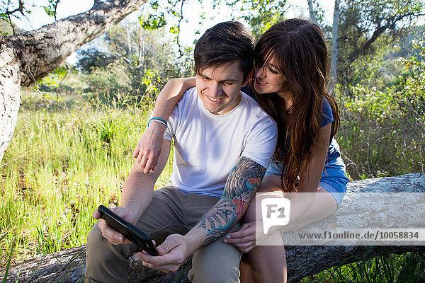 Junges Paar beim Durchstöbern des digitalen Tabletts im Park