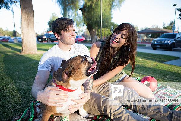 Junges Paar im Park streichelt Bulldogge