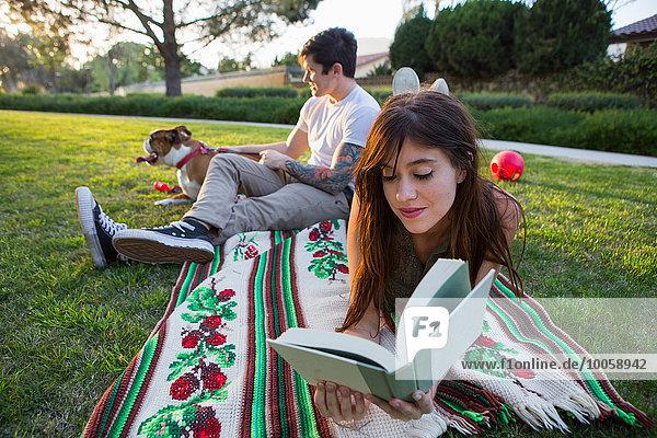 Junge Frau liest Buch  während Freund Haustiere Hund in Park