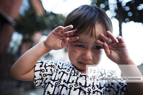 Portrait of boy crying on street
