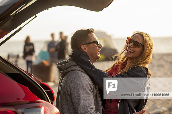 Paar entspannen hinter dem Fahrzeug am Strand