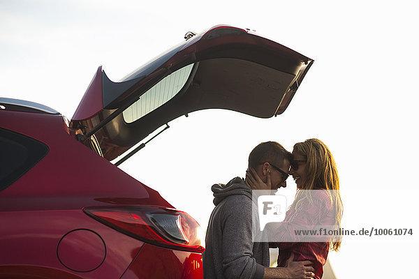 Paar entspannt hinter dem Fahrzeug