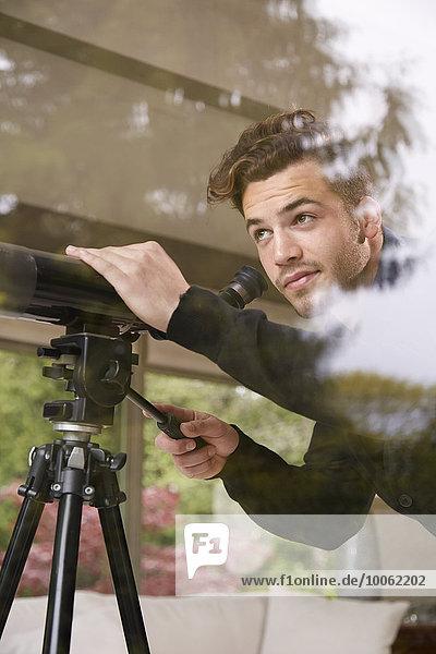 Porträt eines Mannes mit Teleskop aus dem Fenster schauend