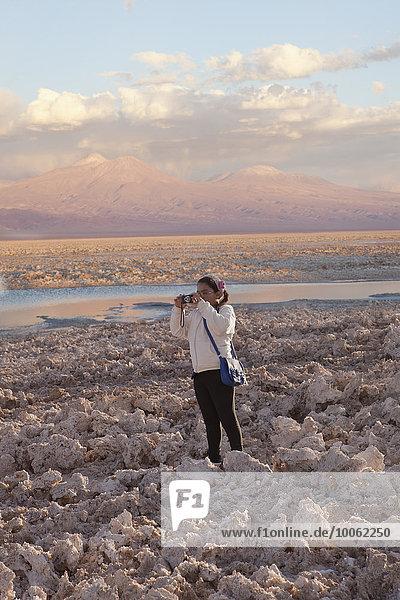 Young girl taking photograph of arid landscape of Salar de Atacama  San Pedro  Atacama  Chile